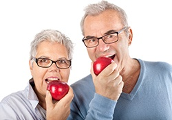 Older man and woman eating red apples