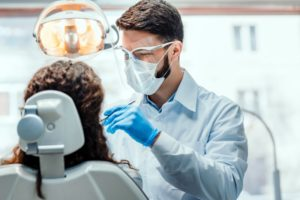 a dentist wearing proper personal protective equipment while treating a female patient