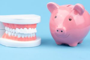 Smiling piggy bank next to dental model, illustrating affordable dentures