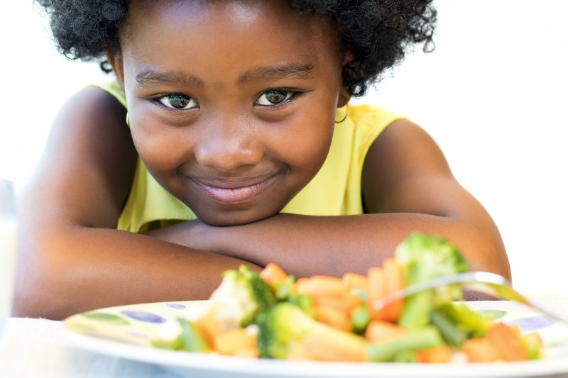Child eating balanced meal with cooked veggies